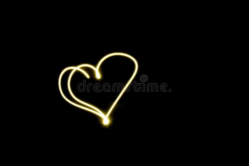 Linha de coração símbolo criado pelo fundo preto claro fotografia de stock