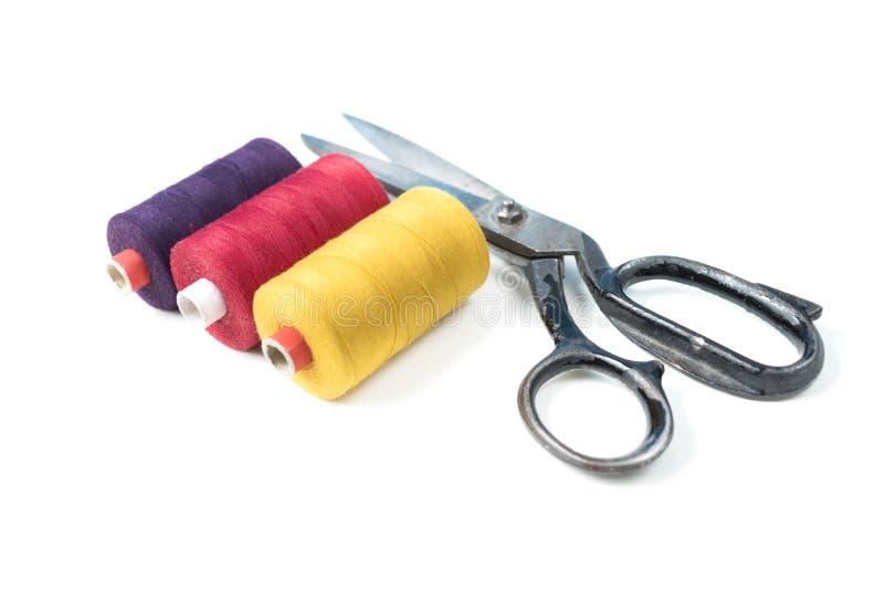 A linha de costura colorida bobina com as tesouras velhas do metal no fundo branco fotografia de stock