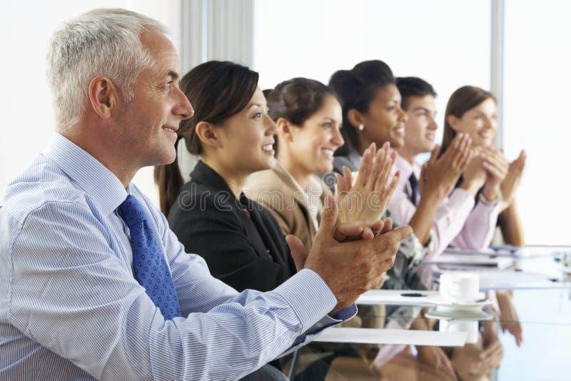 Linha de executivos que escutam a apresentação assentada na tabela de vidro da sala de reuniões foto de stock