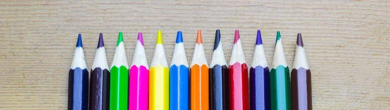 Linha de lápis coloridos no fundo de madeira fotos de stock