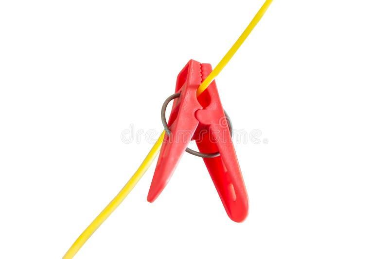 Linha de lavagem plástica vermelha Pegs de roupa em um cabo amarelo isolado no branco fotografia de stock royalty free