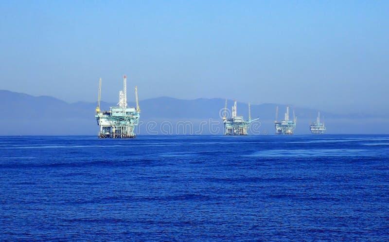 Linha de plataformas petrolíferas fora da costa de Califórnia disparada do oceano fotos de stock
