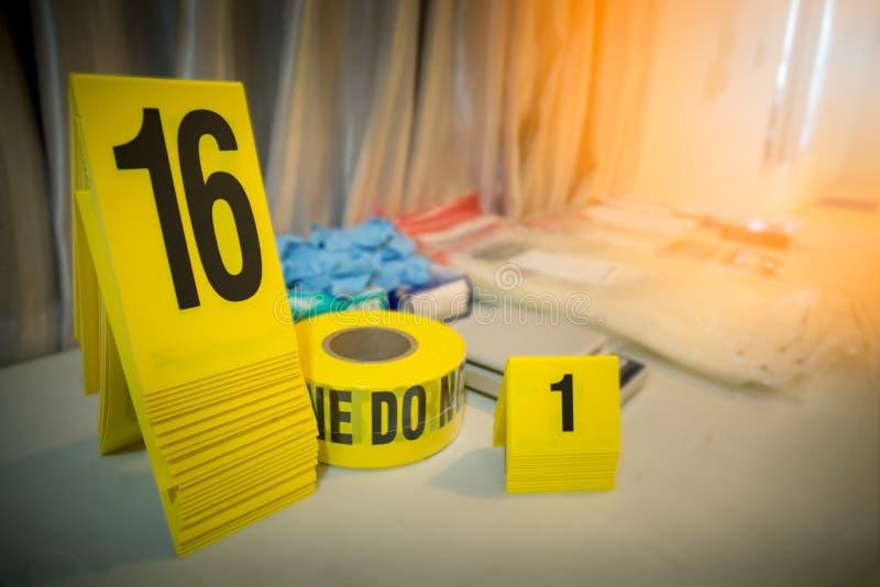 A linha de polícia e o marcador da evidência com ciência forencsic utilizam ferramentas para trás imagem de stock