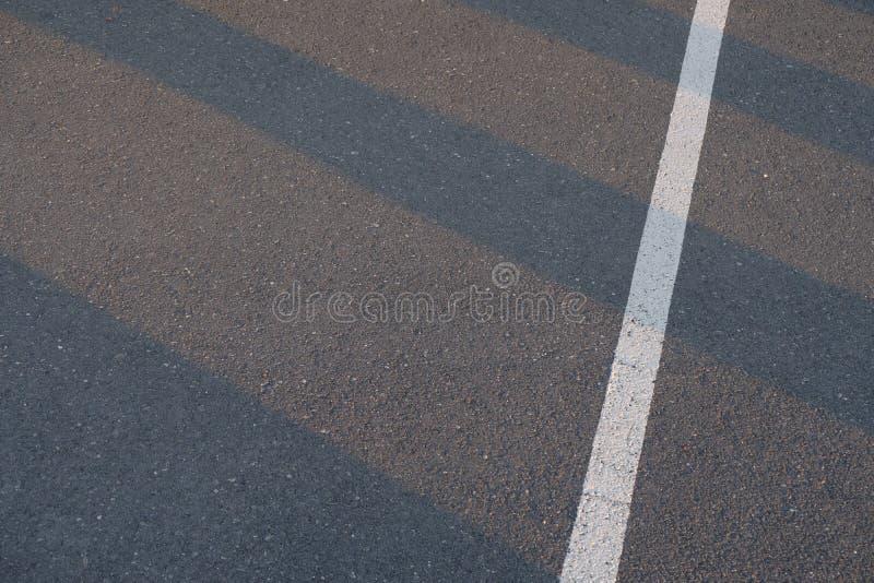 Linha do tráfego pintada sobre a superfície nova do asfalto da estrada com testes padrões do brilho claro do por do sol através d fotografia de stock royalty free