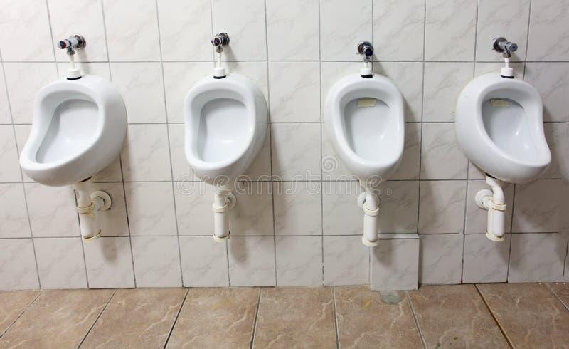 Linha dos mictórios brancos da porcelana em toaletes públicos fotos de stock