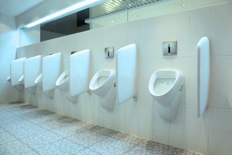 Linha dos urinals brancos da porcelana no toalete foto de stock royalty free