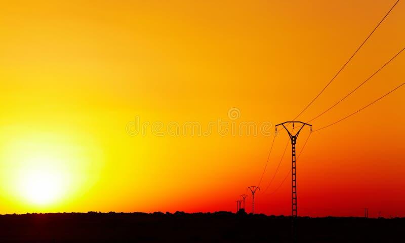 Linha eléctrica elétrica de encontro ao céu colorido no por do sol imagens de stock