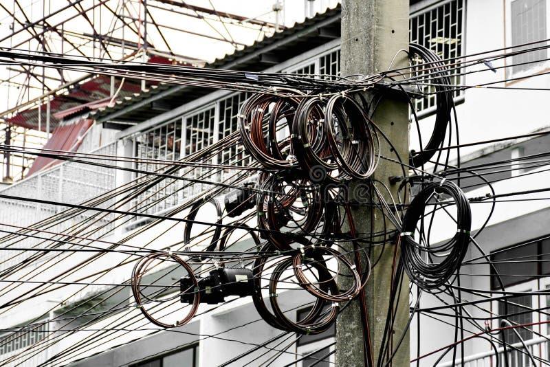 Linha elétrica de Tangle no polo na cidade imagens de stock
