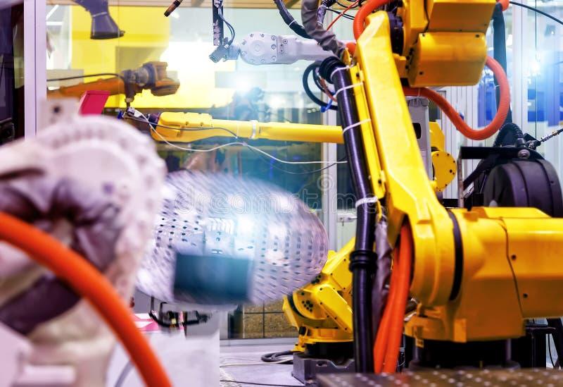Linha industrial com os robôs amarelos em lados, em produção e no processamento das peças de metal, foco slective fotografia de stock royalty free