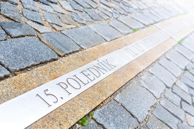 15a linha meridiana na rua cobbled de Jindrichuv Hradec, República Checa Inscrição 15 o polednik significa o 15o meridiano fotografia de stock royalty free