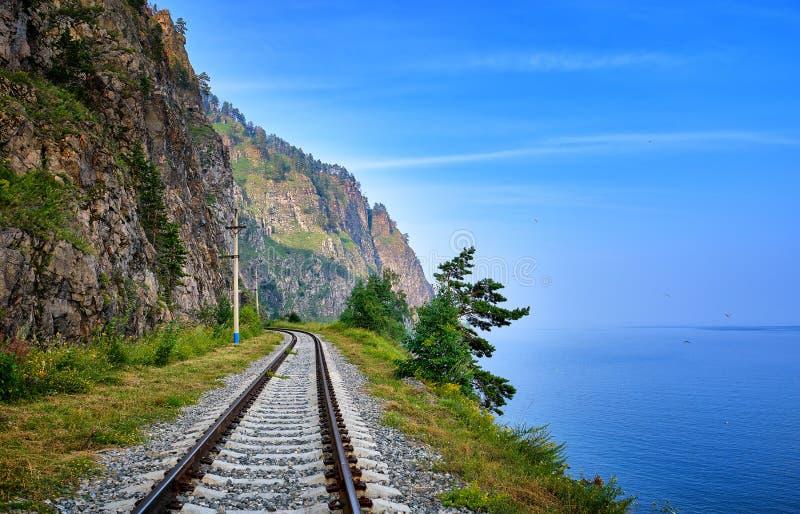 Linha railway de única trilha na borda da terra entre a rocha e o Lago Baikal íngremes fotografia de stock