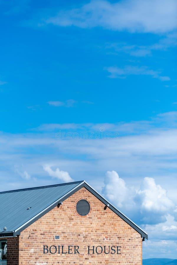 Linha superior do telhado de uma construção de casa da caldeira com céu azul e nuvens imagem de stock