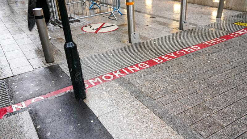Linha vermelha no pavimento com texto NÃO FUMADORES, sinal perto dos pedestres igualmente de informação estão entrando na área de fotos de stock royalty free