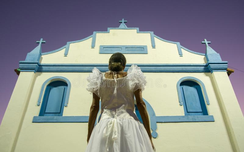 Linhares, Espírito Santo, Brazylia - 4 kwietnia 2016: Starsza kobieta ubrana w suknię ślubną patrząca na kościół Regencji fotografia royalty free