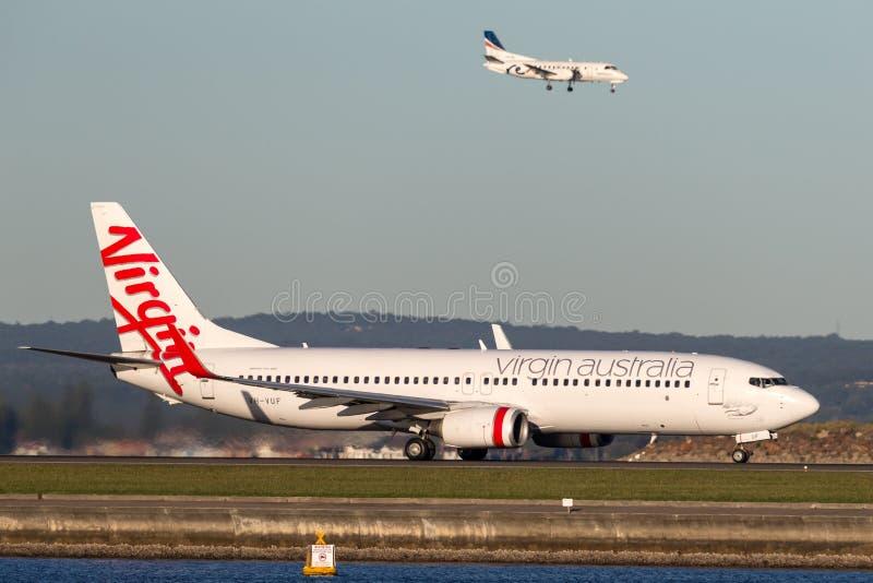 Linhas aéreas Boeing de Austrália do Virgin 737-800 aviões em Sydney Airport com REX Saab 340 que aterra atrás imagem de stock royalty free