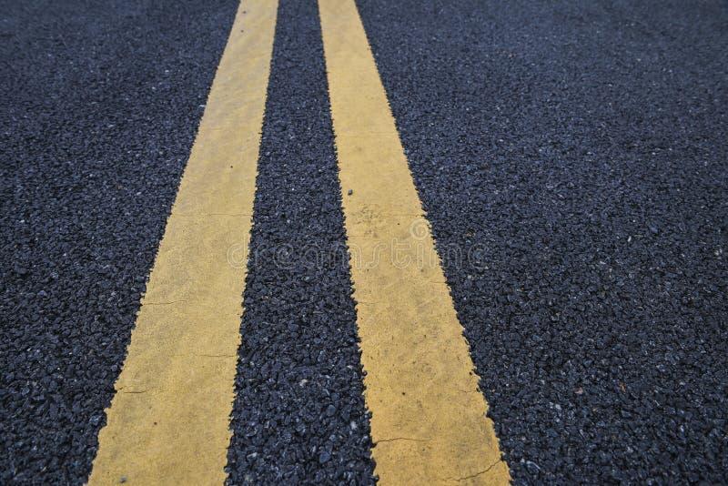 Linhas amarelas marcação do tráfego na estrada asfaltada fotografia de stock royalty free
