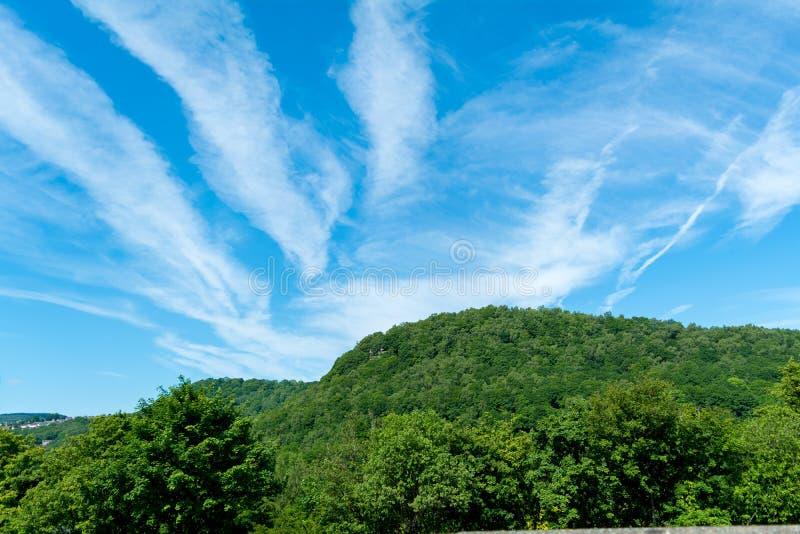 Linhas da nuvem no céu azul sobre a paisagem verde fotos de stock