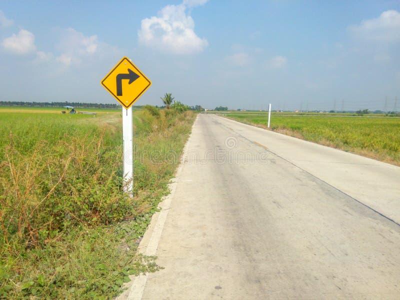 Linhas de acesso da estrada, batendo o lado de um campo com sinais amarelos fotos de stock