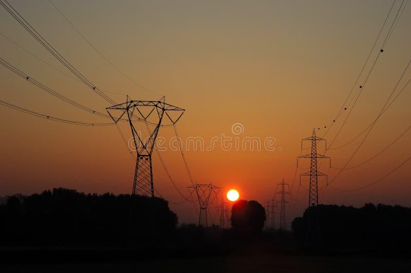 Linhas de alta tensão do por do sol foto de stock