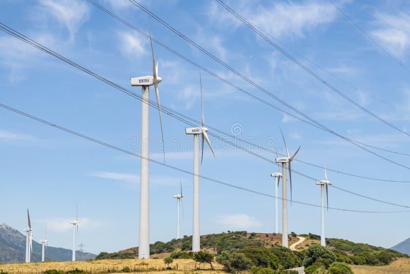 Linhas de alta tensão e Espanha de Málaga do windfarm do Los Llanos dos moinhos de vento foto de stock