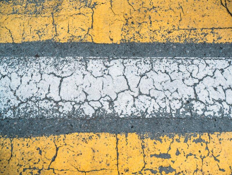 Linhas de pintura amarelas e brancas rachadas na textura cinzenta da estrada asfaltada, na vista superior como o fundo do grunge  imagem de stock royalty free