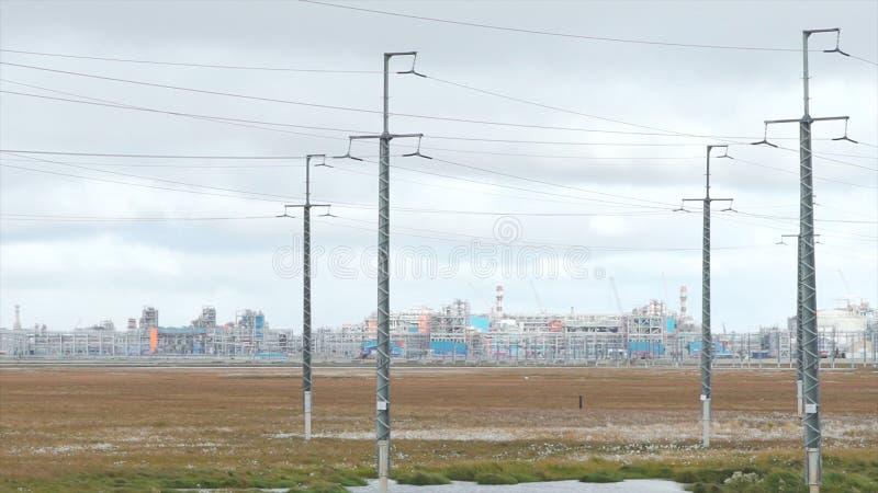 Linhas de transmissão e fundo da fábrica vídeo Indústria de petróleo e gás, fábrica da refinaria, área da instalação petroquímica imagens de stock