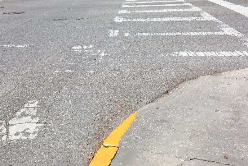 Linhas desvanecidas da faixa de travessia na rua velha da cidade foto de stock