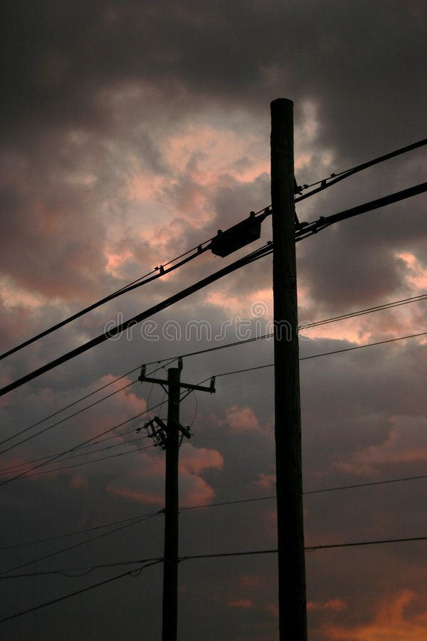 Linhas eléctricas de encontro ao céu nebuloso foto de stock