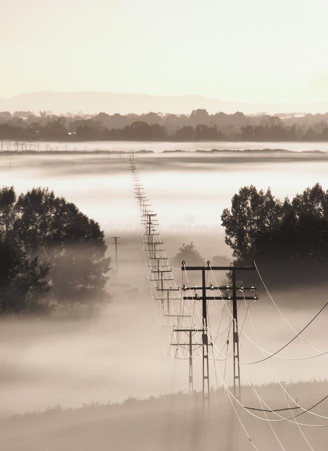 Linhas eléctricas na névoa imagens de stock
