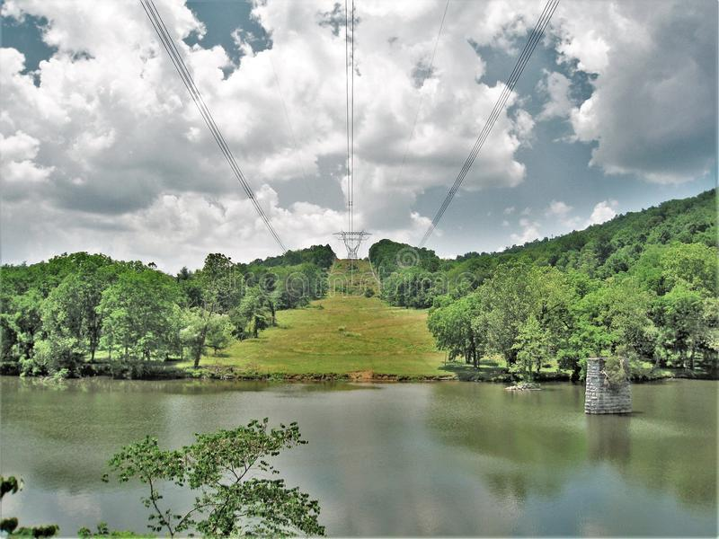 Linhas elétricas através do rio novo em Virgínia foto de stock