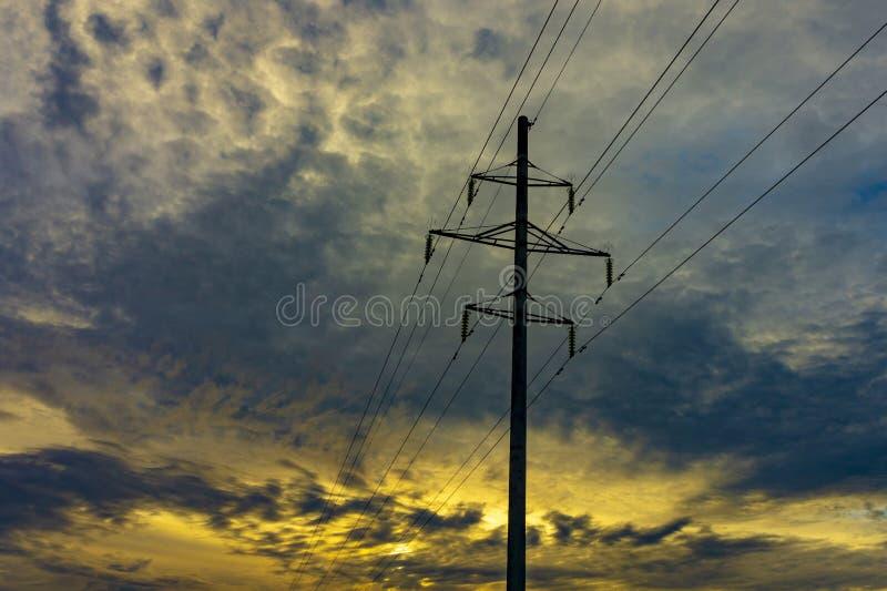Linhas elétricas da eletricidade contra um céu do por do sol imagem de stock