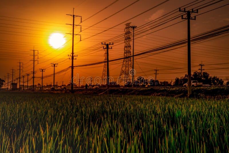 Linhas elétricas de alta tensão do polo e de transmissão no tempo do por do sol com o céu e as nuvens alaranjados e vermelhos Arq imagens de stock royalty free