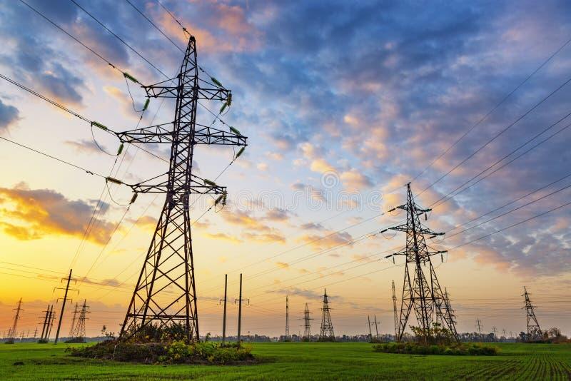 Linhas elétricas de alta tensão no por do sol imagens de stock