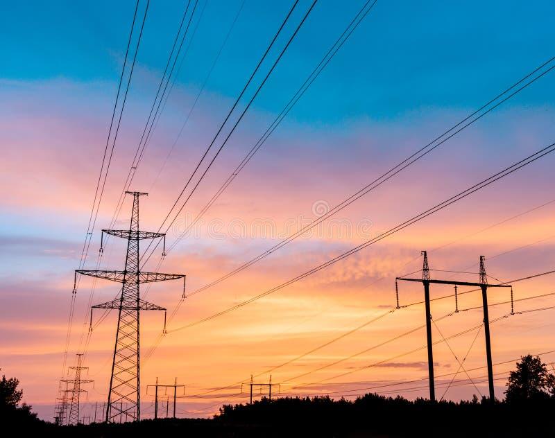 Linhas elétricas de alta tensão no por do sol Estação da distribuição da eletricidade Torre elétrica de alta tensão da transmissã imagens de stock royalty free