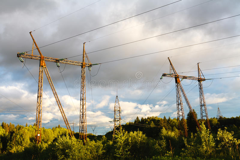 Linhas elétricas de alta tensão no por do sol sta da distribuição da eletricidade fotografia de stock royalty free