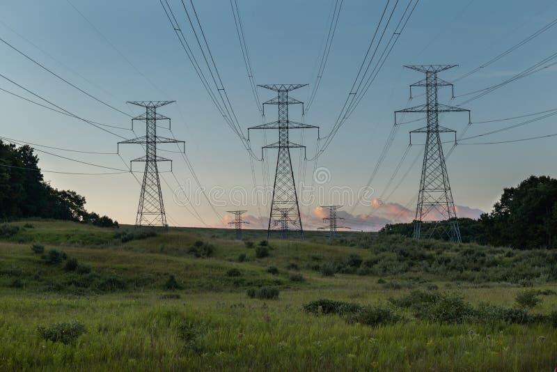 Linhas elétricas do poder da hidro planta elétrica por campos no por do sol do nascer do sol fotografia de stock royalty free