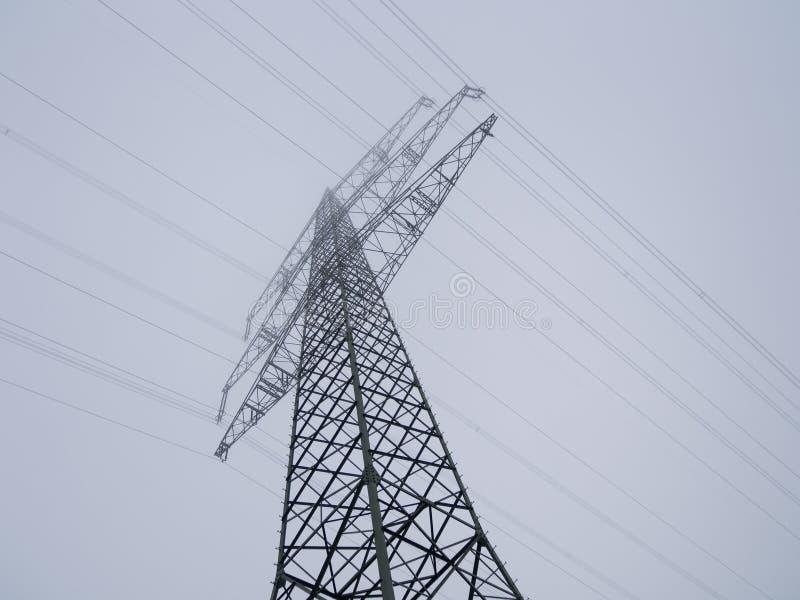 Linhas elétricas no céu nevoento fotografia de stock royalty free