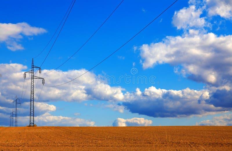 Linhas elétricas que correm através de um campo de trigo com o céu azul fotos de stock