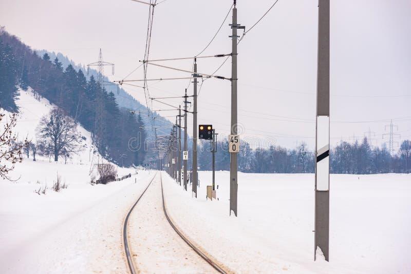 Linhas el?tricas da estrada de ferro e os campos cobertos de neve em uma paisagem c?nico da montanha do inverno, maci?o de Dachst imagem de stock