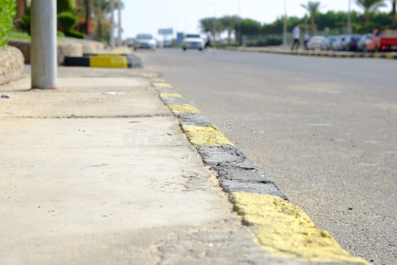 Linhas pretas e amarelas no asfalto velho, superfície de estrada imagem de stock