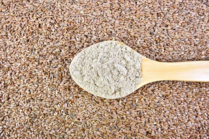 Linho da farinha na colher de madeira em sementes foto de stock