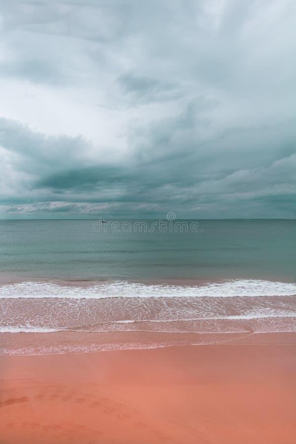 Linia horyzontu plaża z różowym piaskiem i chmurnym niebem obraz royalty free