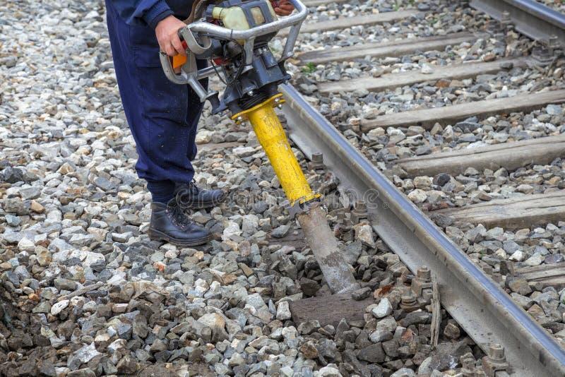 Linia kolejowa pracownik używa pionowo wibrację majstruje obrazy royalty free