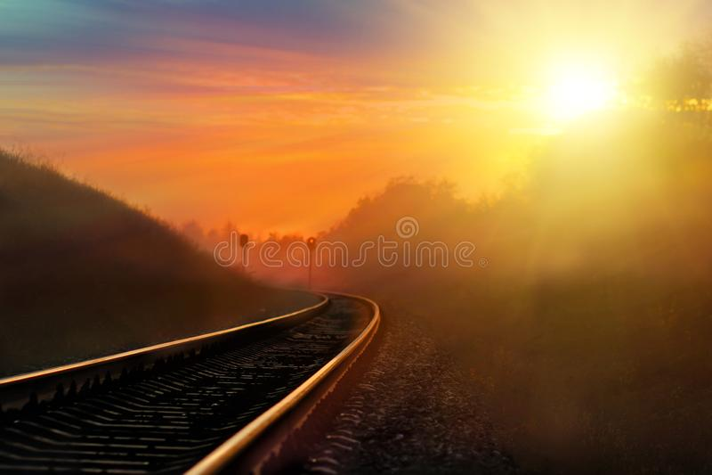 Linia kolejowa przeciw pięknemu niebu przy zmierzchem Przemysłowy krajobraz z stacją kolejową, kolorowym niebieskim niebem, drzew fotografia royalty free