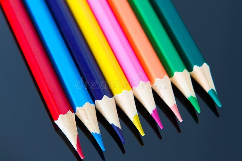 Linia kolorowi drewniani ołówki na czarnym tle obrazy royalty free