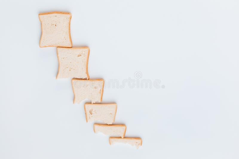 Linia plasterków chleba, które stają się coraz mniejsze, na białym tle obrazy royalty free