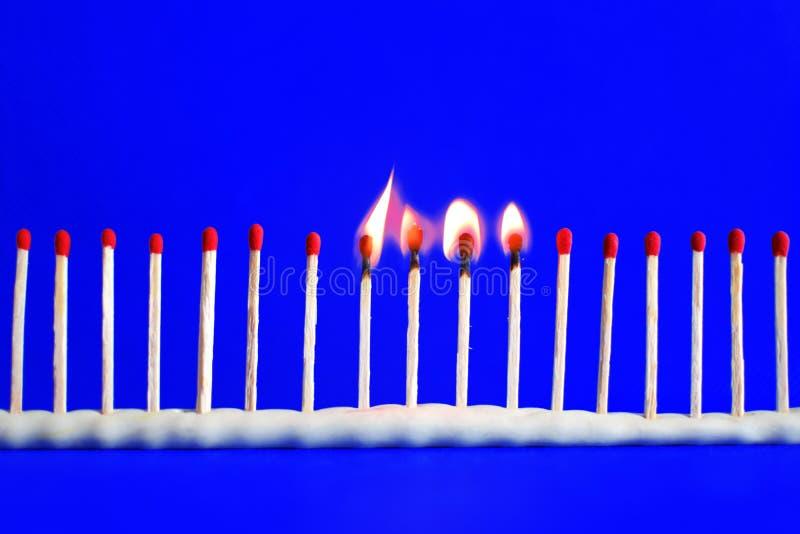 Linie des roten unbenutzten und vier brennenden Sicherheitsmatches auf Blau lizenzfreie stockfotos