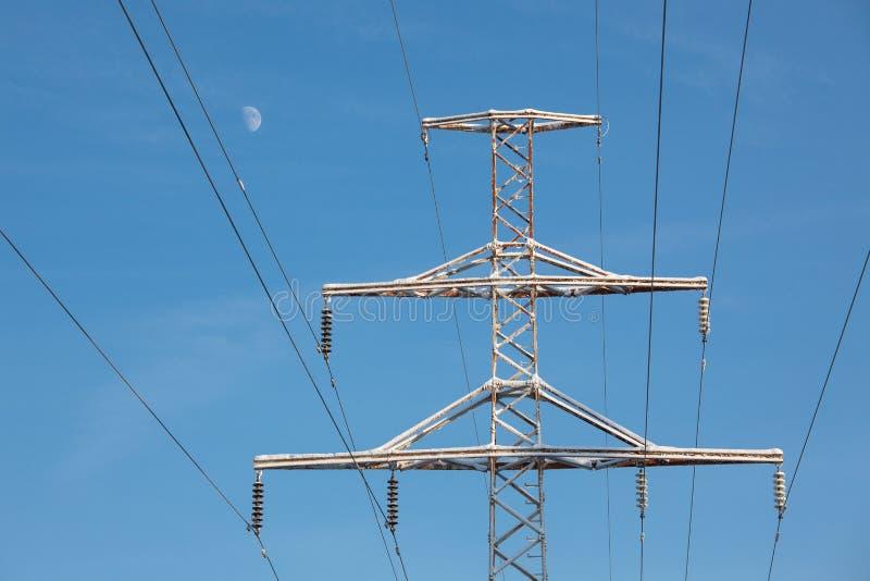 Linie energetyczne rozjaśniają niebieskie niebo i księżyc przy zimą zdjęcie stock