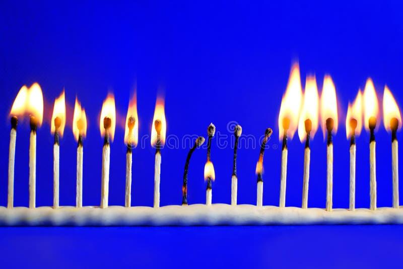 Linie von siebzehn brennendem Sicherheitsmatch auf Blau lizenzfreies stockbild