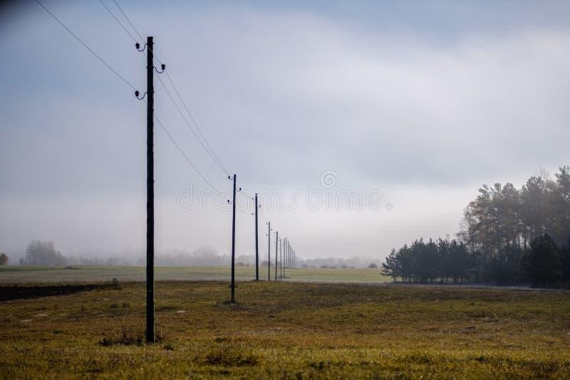 linii energetycznej elektryczności słupy w kraju zdjęcia stock